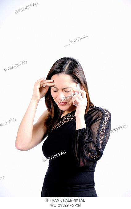 Woman dressed in black talking on the telephone and seems very sad and holding her head  She is of mixed ethnicity