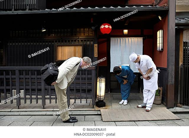 Senior Japanese hostess, cook and Caucasian man bowing
