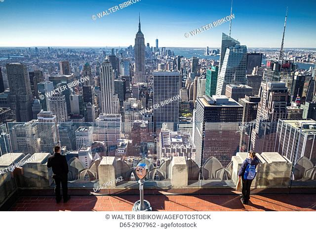 USA, New York, New York City, Mid-Town Manhattan, elevated view of The Empire State Building and visitors to the Top of The Rock rooftop