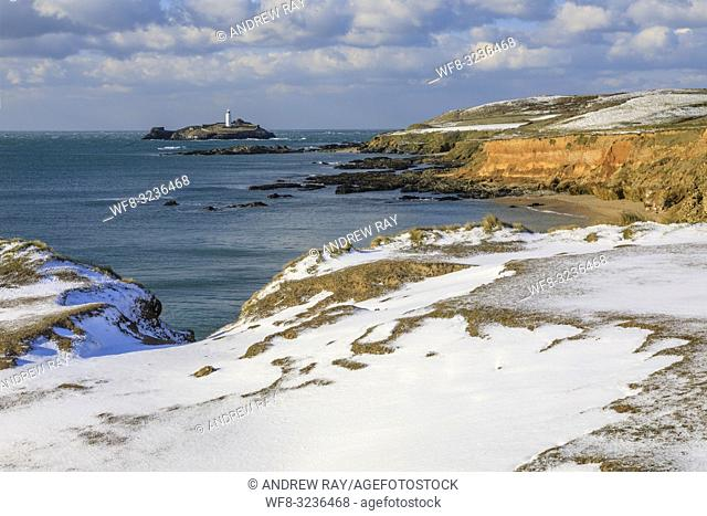 Godrevy lighthouse on the eastern side of St Ives Bay in Cornwall captured after a snowfall on an afternoon in late February