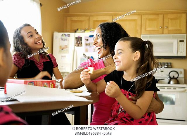 Laughing family sitting in kitchen