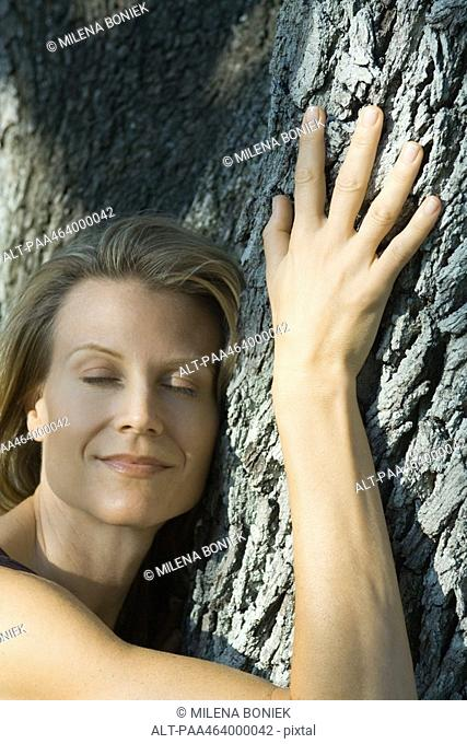 Woman hugging tree, eyes closed, smiling, head and shoulders