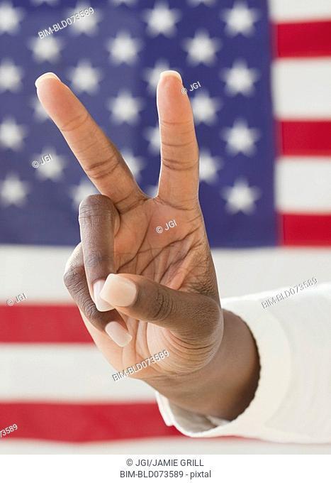 African woman making peace symbol near American flag