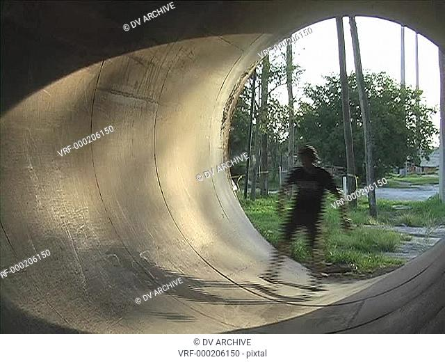 A skateboarder rides inside of a drainage tunnel