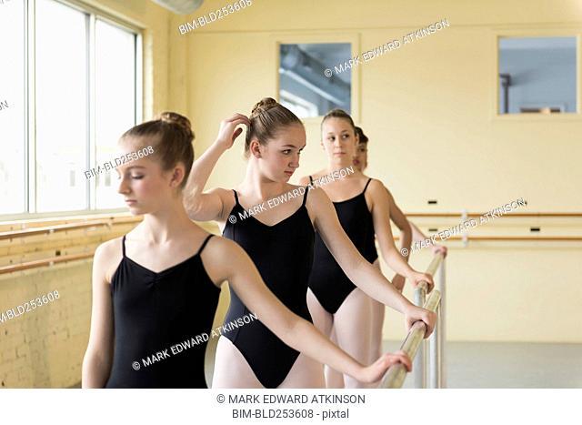 Girls holding barre in ballet studio
