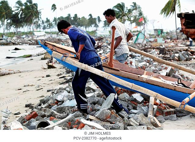 Fishermen dragging a small fishing boat to the sea after the Indian Ocean tsunami in 2004; Meulaboh, Aceh Province, Sumatra, Indonesia