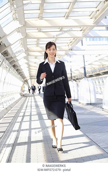 Japan, Honshu, Tokyo, Businesswoman walking on skybridge, smiling