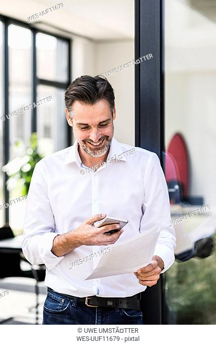 Smiling businessman looking at cell phone and documents