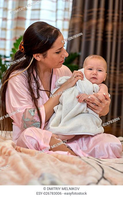 Young mother and her sweet baby with towel sits on a bed at home