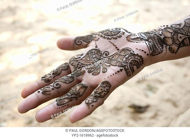 Fresh henna paste applied to a young woman's hand