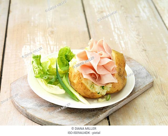 Wafer thin ham in baked potato with salad leaves and spring onions on white plate and whitewashed cutting board