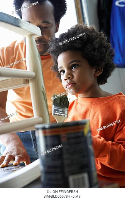 African father watching son paint rocking chair