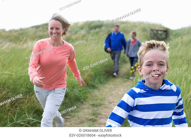 Family of four running down the sanddunes onto the beach. They are wearing casual clothing and smiling