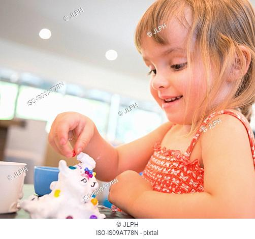 Young girl playing messy play at table