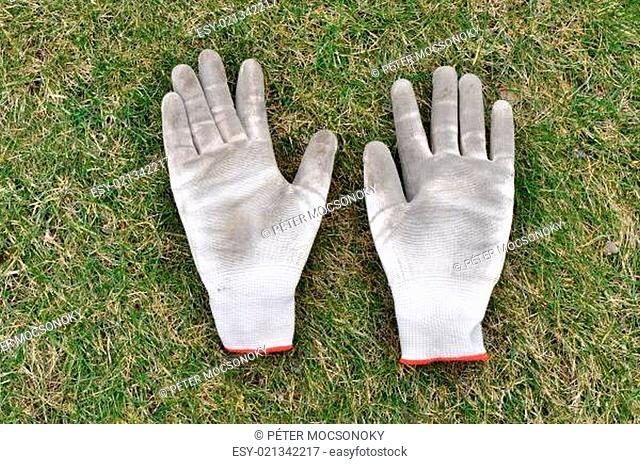 Dirty gardening gloves on the grass