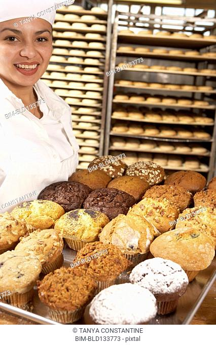 Hispanic baker carrying tray of muffins in bakery