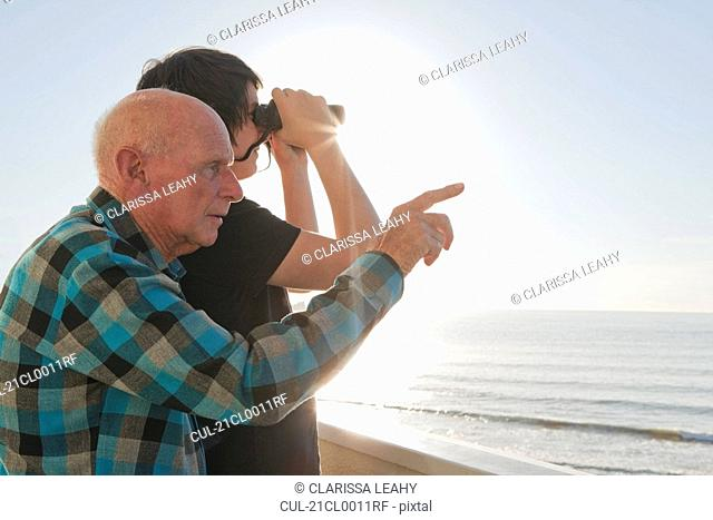 Old man and grandson looking out to sea