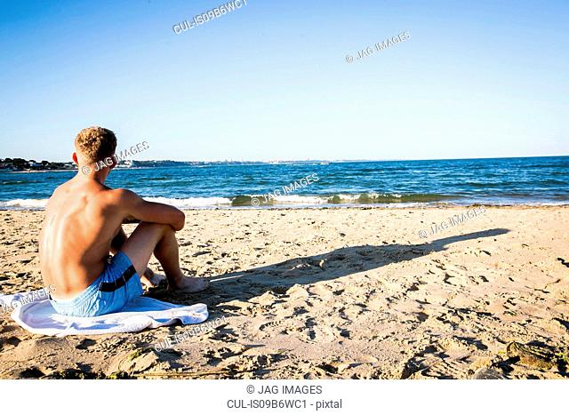 Young man sitting on beach looking out to sea