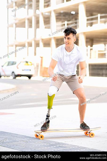 Smiling amputated man skateboarding on street
