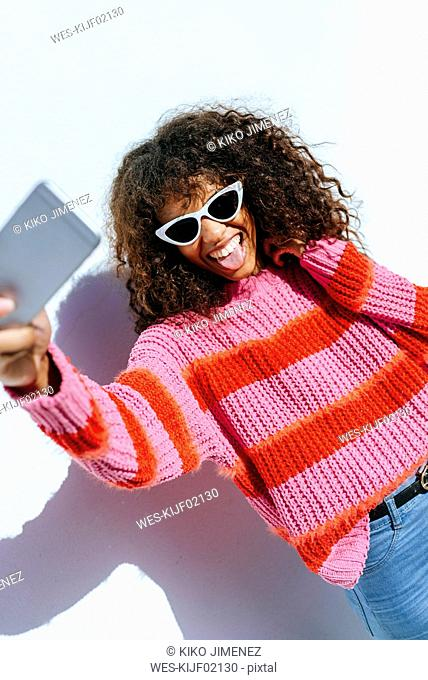 Portrait of young woman wearing sunglasses taking selfie with mobile phone
