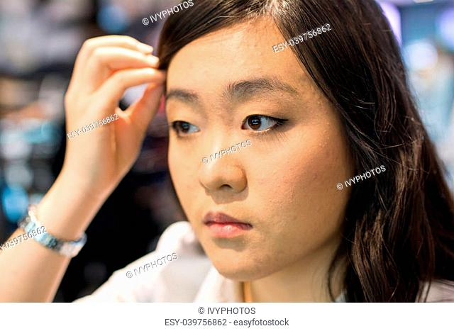 Young Asian womna checking herself while applying cosmetics