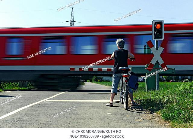 Woman with bicycle in front of a railway crossing