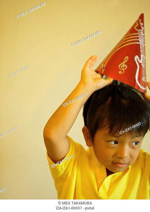 Boy wearing a birthday hat