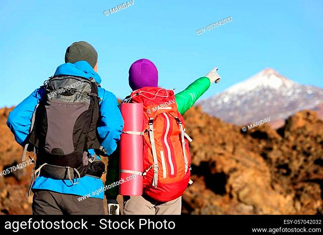 Hikers looking at view pointing hiking in mountain. People hiker couple in nature landscape trekking wearing backpacks. Woman and man on volcano Teide, Tenerife