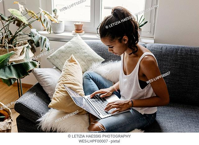 Young woman sitting on the couch at home using laptop