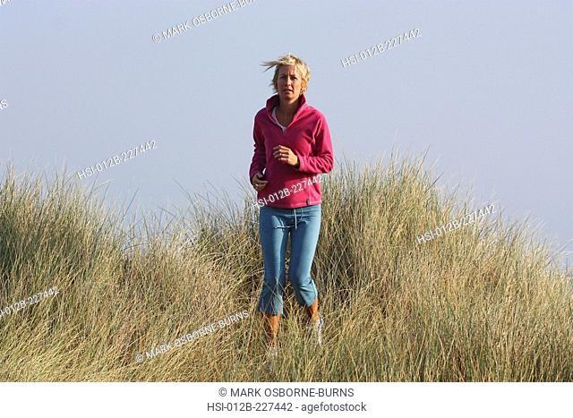 Young blonde woman outdoors. Jogging through long grass