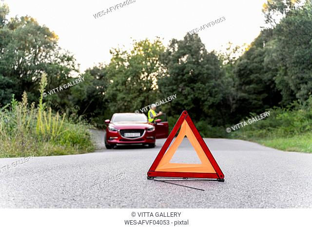 Warning triangle in front of a senior man's broken car on a country road