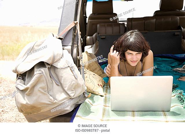 Woman using laptop in vehicle