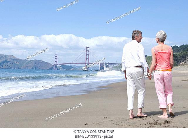 Senior Caucasian couple walking by Golden Gate Bridge, San Francisco, California, United States