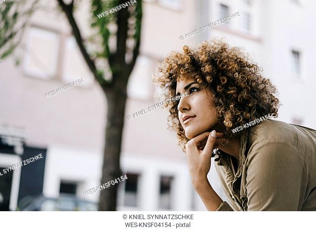 Woman with hand on chin, thinking, portrait