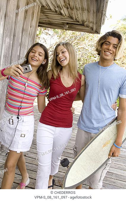 Portrait of a teenage boy smiling with two teenage girls looking at a mobile phone