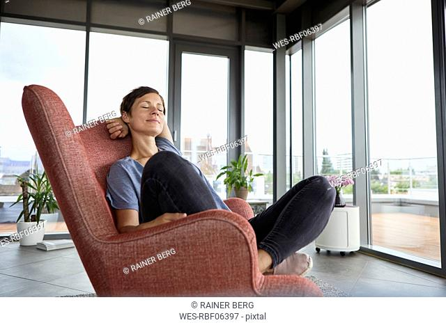 Woman sitting in armchair at home relaxing with closed eyes