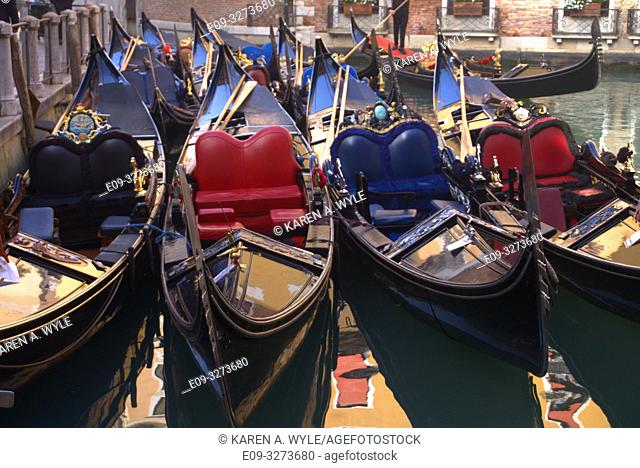 crowded parking area for gondolas, reflections in water between them, Venice, Italy