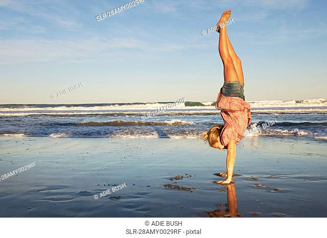 Girl doing handstand on the beach