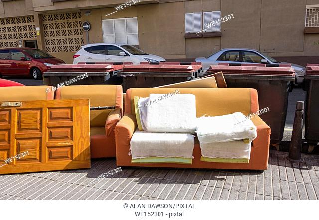 Furniture left next to containers used for household non - recyclable waste in residential street in Las Palmas, Gran Canaria, Canary Islands