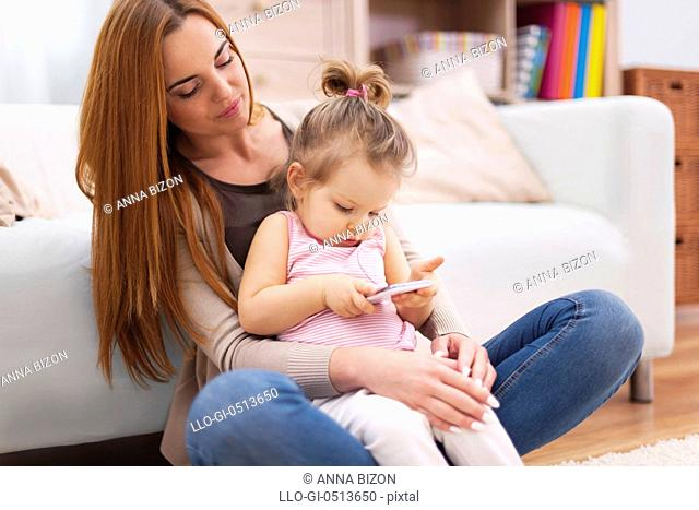 Mother and baby with mobile phone at home. Debica, Poland