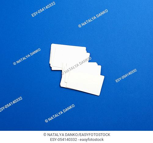 stack of rectangular white blank business cards on a blue background. Corporate business concept