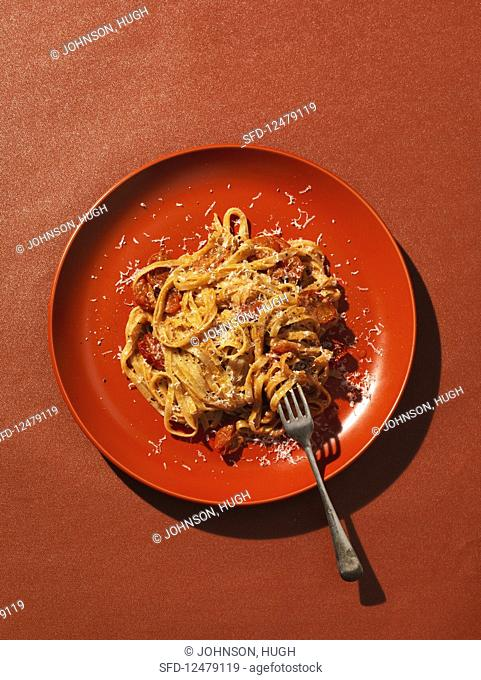 Pasta with tomato on red plate