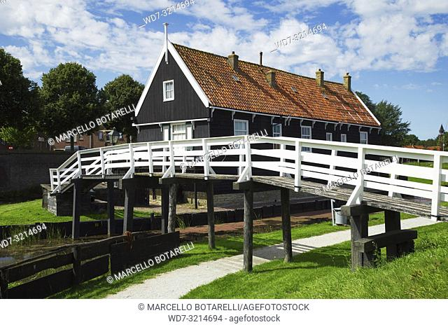 Traditional fisherman's house with white wooden bridge, trees and grass, clouds and blue sky in Enkhuizen, small town in Netherlands