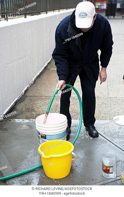 Residents without power from Hurricane Sandy fill buckets of water to cook and flush toilets with at a hose set up for them in Confucius Plaza in Chinatown in...