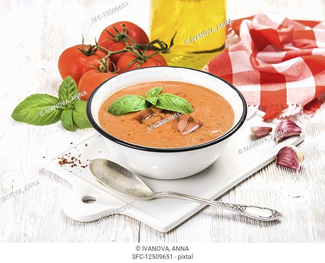 Cold gazpacho soup in bowl with ice with hot pepper and basil