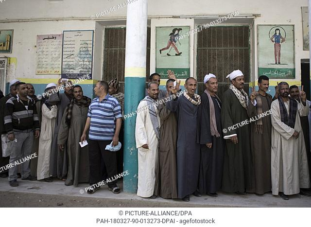 Egyptian men queue up outside a polling station to cast their votes at a polling station on the second day of the 2018 Egyptian presidential elections, in Giza