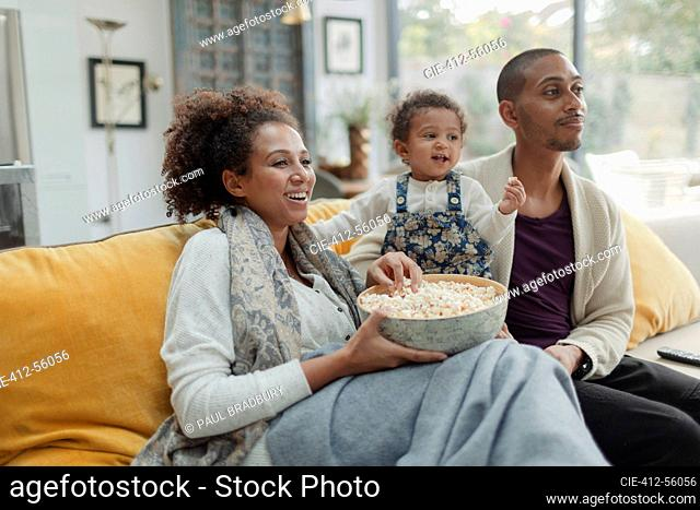 Couple with baby daughter eating popcorn and watching TV on sofa