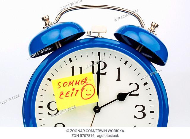 Ein Wecker mit einem Zettel zur Erinnerung auf die Uhrumstellung zur Sommerzeit