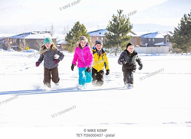 Children (8-9, 10-11) running in snow