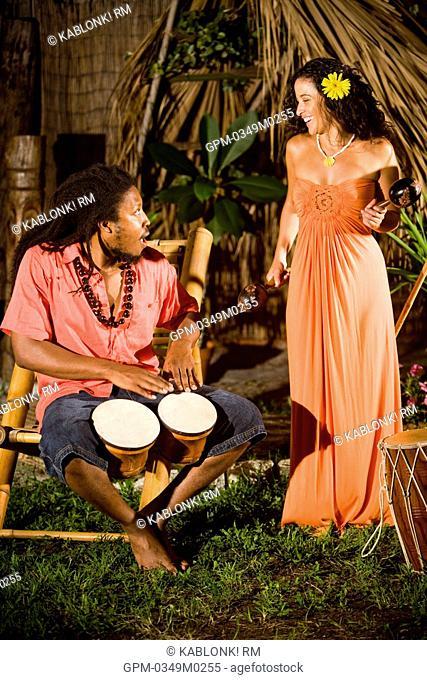 Young Jamaican man playing bongo drums and Hispanic woman with maracas on tropical island